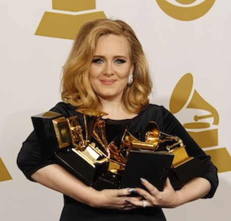 Adele cradles her trophies at the 54th Annual Grammy Awards.