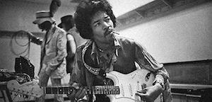 Guitarist Jimi Hendrix in a studio with a Fender stratocaster.