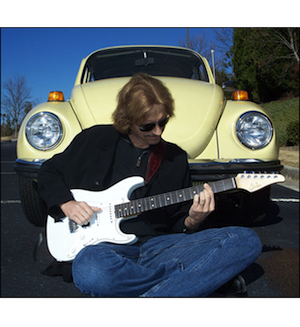Guitarist Steve Freeman with a Volkswagon Bug in the background.
