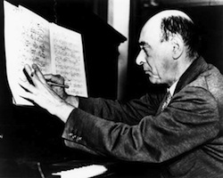 Composer Arnold Schoenberg writing music at the piano.