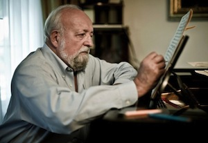 Composer Krzysztof Penderecki writing at the piano.