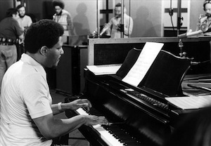 Pianist McCoy Tyner performing in a studio with other musicians.