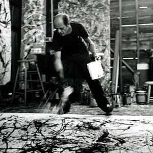 Jackson Pollock throwing paint on a canvas on the floor.